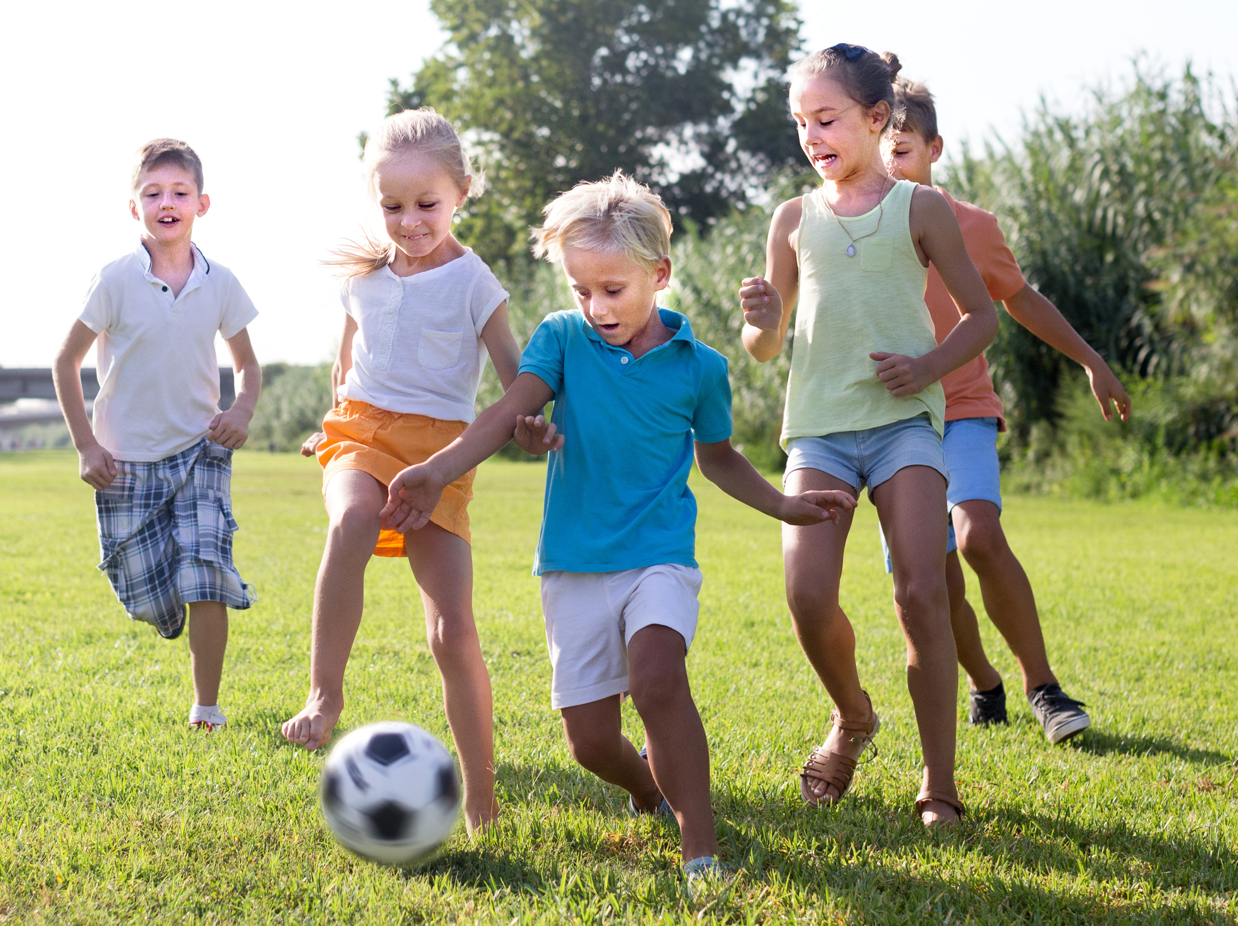 active kids having fun and kicking football outdoors  on summer day